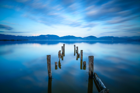 Wooden pier or jetty remains on a blue lake sunset and cloudy sky reflection on water  Long exposure, Versilia Massaciuccoli Lake, Tuscany, Italy  Stock Photo