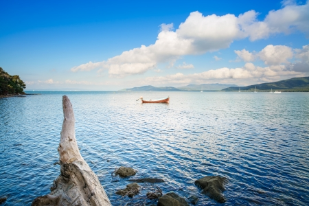 seafront: Small wooden boat and tree trunk in a sea bay on sunset  Punta Ala, Tuscany, Italy Stock Photo