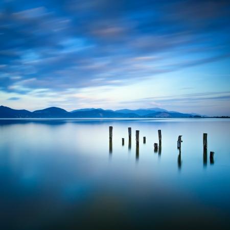 Träbrygga eller brygga kvar på en blå sjö solnedgång och mulen himmel reflektion på vatten Lång exponering, Versilia Massaciuccoli sjön, Toscana, Italien