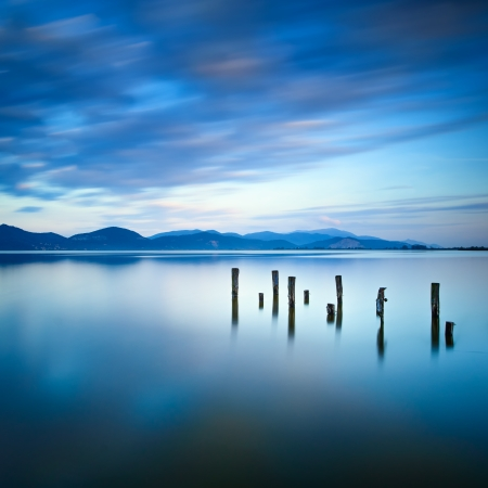 Wooden pier or jetty remains on a blue lake sunset and cloudy sky reflection on water  Long exposure, Versilia Massaciuccoli Lake, Tuscany, Italy  Stock fotó