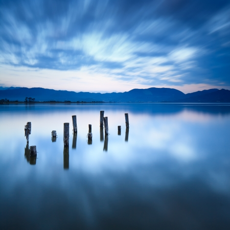 old pier: Wooden pier or jetty remains on a blue lake sunset and cloudy sky reflection on water  Long exposure, Versilia Massaciuccoli Lake, Tuscany, Italy  Stock Photo