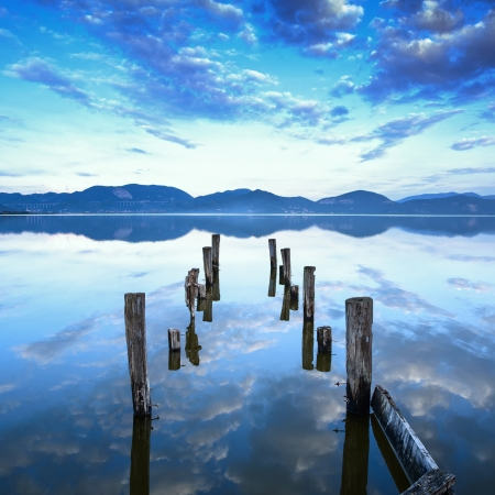 old pier: Wooden pier or jetty remains on a blue lake sunset and cloudy sky reflection on water  Versilia Massaciuccoli Lake, Tuscany, Italy