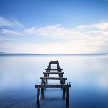 Träbrygga eller brygga kvar på en blå sjö solnedgång Lång exponering fotografering Stockfoto