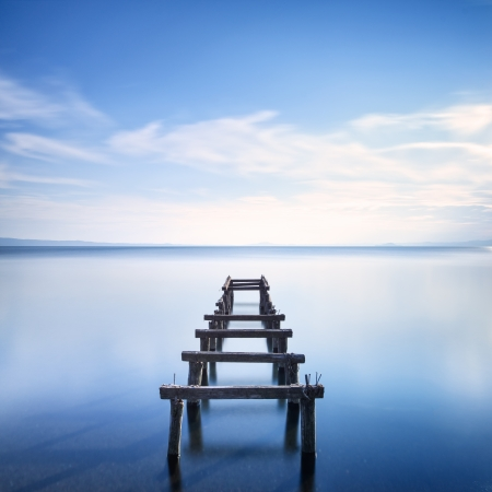 remains: Wooden pier or jetty remains on a blue lake sunset  Long Exposure photography Stock Photo