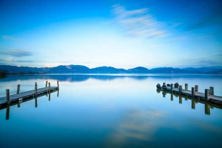 Two Wooden pier or jetty on a blue lake sunset and cloudy sky reflection on water  Long exposure, Versilia Massaciuccoli Lake, Tuscany, Italy  스톡 콘텐츠