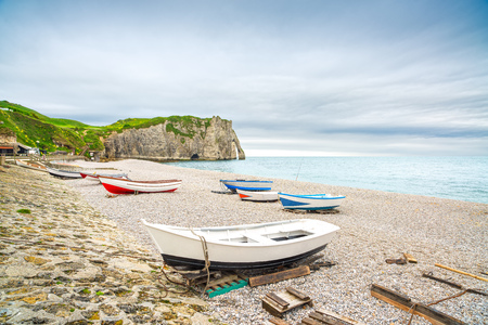 crepuscle: Etretat village, its bay beach, Aval cliff and boats  Normandy, France, Europe  Stock Photo