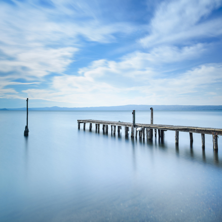 Wooden pier or jetty remains on a blue lake sunset  Long Exposure photography Imagens