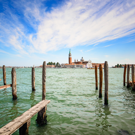 Venice lagoon, wooden poles and San Giorgio Maggiore church landmark on background  Italy, Europe  photo