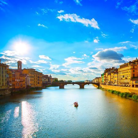 trinita: Florence or Firenze, Ponte Santa Trinita medieval Bridge landmark on Arno river and a boat, sunset landscape  Tuscany, Italy