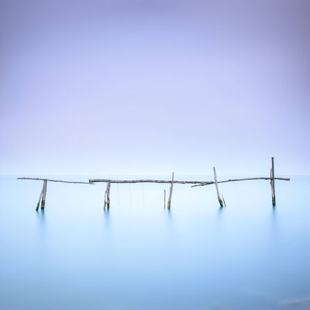 quiet scenery: Fishing poles for clams and mussels and soft water on a quiet water landscape  Long exposure photography