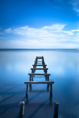 Wooden pier or jetty remains on a blue lake sunset  Long Exposure photography Stock Photo