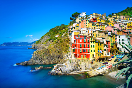 cinque: Riomaggiore village on cliff rocks and sea at sunset , Seascape in Five lands, Cinque Terre National Park, Liguria Italy Europe  Square format  Long Exposure Stock Photo