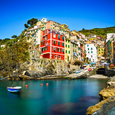 Riomaggiore village on cliff rocks and sea at sunset , Seascape in Five lands, Cinque Terre National Park, Liguria Italy Europe  Long Exposure Stock Photo