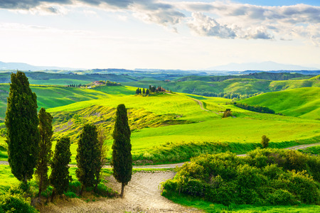 toscana: Tuscany, rural sunset landscape  Countryside farm, cypresses trees, green field, sun light and cloud  Volterra, Italy, Europe  Stock Photo