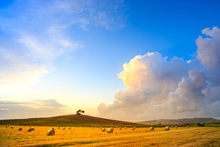 Tuscany, Maremma typical countryside sunset landscape and thunderstorm cloud  Hill, trees, straw bales and rural tower  photo