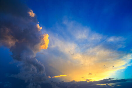 approaching: Dramatic sunset sky with yellow, blue and orange approaching thunderstorm clouds  Stock Photo