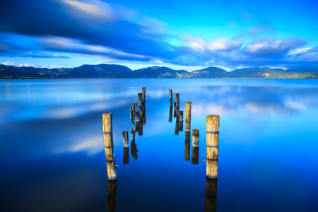Wooden pier or jetty remains on blue lake sunset and sky reflection water  Long exposure, Versilia Massaciuccoli, Tuscany, Italy