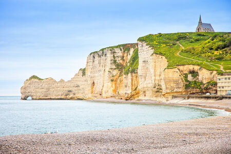 Etretat cliff and church landmark and its beach on morning  Normandy, France, Europe  photo