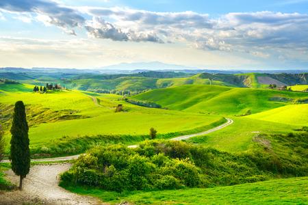 토스카나, 농촌 일몰 풍경입니다. 시골 농장, 푸른 나무, 녹색 필드, 태양 빛의 구름. 테라, 이탈리아, 유럽.