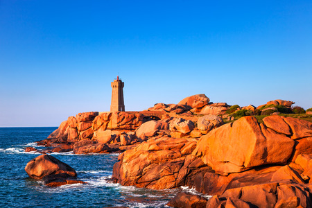Ploumanach Mean Ruz lighthouse red sunset in pink granite coast, Perros Guirec, Brittany, France