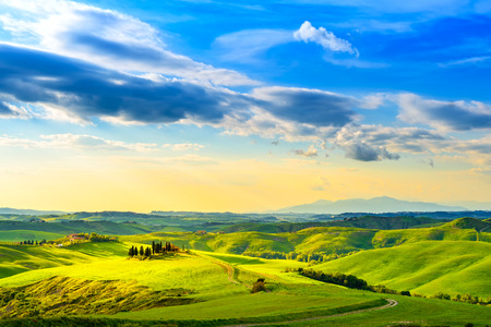 rolling landscapes: Tuscany, rural sunset landscape. Countryside farm, cypresses trees, green field, sun light and cloud. Volterra, Italy, Europe.