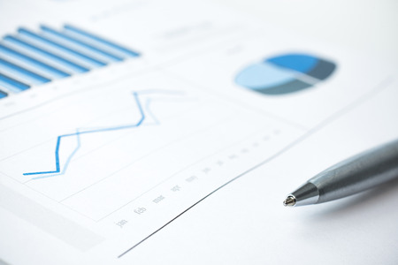 stock listing: Business data report and chart close up. Montly stats. Ink color print paper and pen. Selective Focus. Blue toned Stock Photo