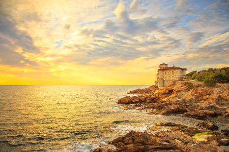 Boccale castle landmark on cliff rock and sea on warm sunset. Tuscany, Italy, Europe.