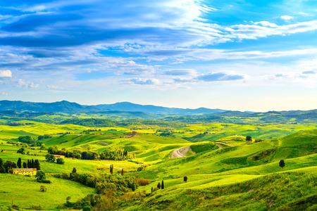 Toscana, paisaje rural sunset. Campo de granja, cipreses, árboles de campo verde, luz del sol y las nubes. Volterra, Italia, Europa.