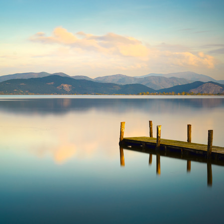 the long lake: Wooden pier or jetty and on a blue lake sunset and cloudy sky reflection on water. Long exposure, Versilia Massaciuccoli Lake, Tuscany, Italy.