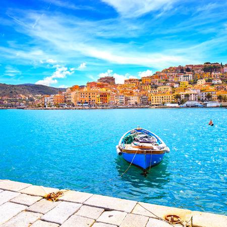 Wooden small old boat in Porto Santo Stefano seafront, italian travel destination. Monte Argentario, Tuscany, Italy.