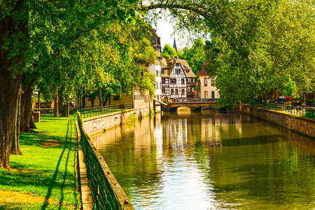 Strasbourg, water canal in Petite France area. Half timbered houses and trees in Grand Ile. Alsace, France.