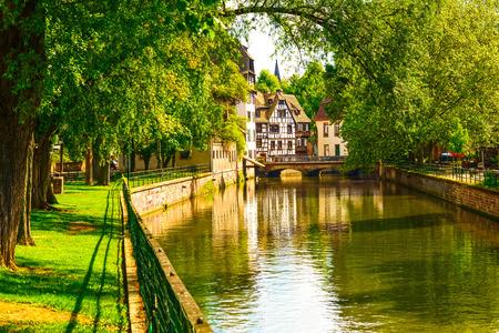 Strasburg, woda kanał w Petite France obszarze. Pół konstrukcji szkieletowej domów i drzew w Grand Ile. Alzacja, Francja.