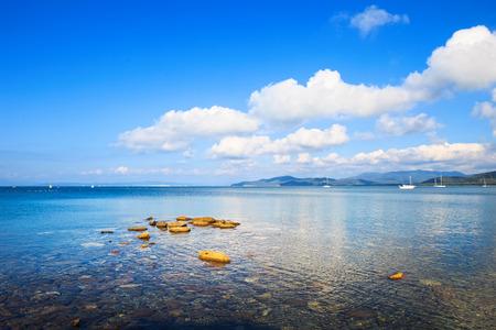 Rocks and yachts in a sea bay. Punta Ala beach, Maremma Tuscany, Italy