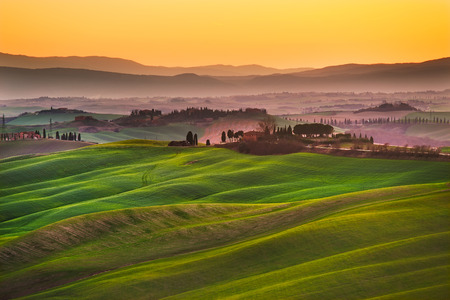 Tuscany, rolling hills on sunset. Crete Senesi rural landscape and sunlight. Green fields, a farm with trees. Siena, Italy Standard-Bild