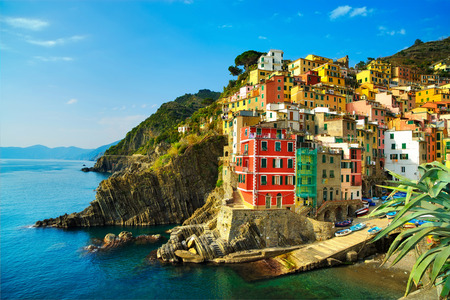 Riomaggiore village on cliff rocks and sea at sunset., Seascape in Five lands, Cinque Terre National Park, Liguria Italy Europe. Long Exposure photo