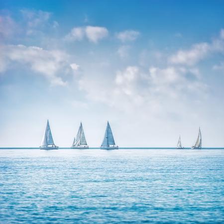 nautical: Sailing boat yacht or sailboat group regatta race on sea or ocean water. Panoramic view.
