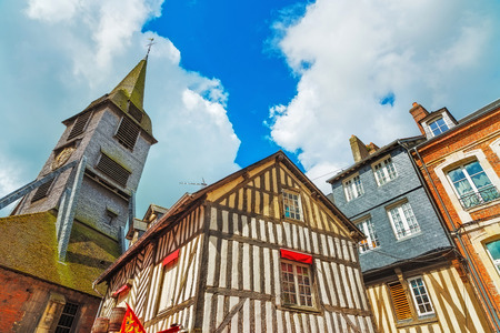 Old traditional wooden half timbered facades and church in Honfleur. Normandy, France, Europe. photo