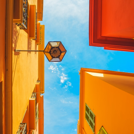 blue facades sky: Urban abstract. Street lamp, red yellow orange house facades and blue sky background. Bottom view