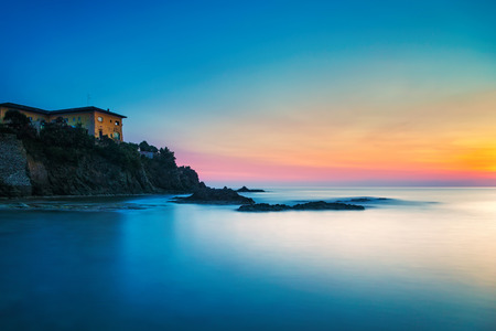 crepuscle: Castiglioncello travel destination, old building on the rocks and sea on sunset. Tuscany, Italy, Europe. Long Exposure