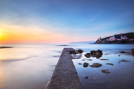 crepuscle: Castiglioncello travel destination, concrete pier in the bay, rocks and sea on sunset. Tuscany, Italy, Europe. Long Exposure Stock Photo