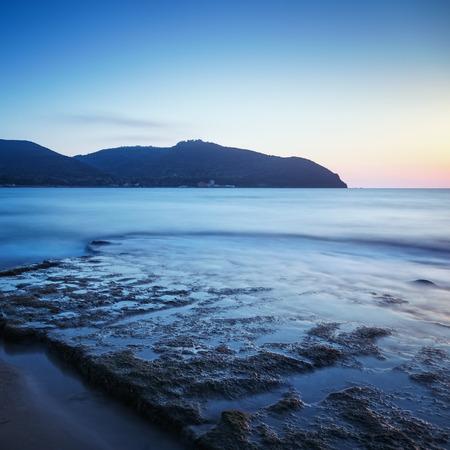 crepuscle: Baratti bay, travel destination, headland hill, rocks and sea on sunset. Tuscany, Italy, Europe. Long Exposure