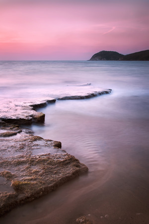 crepuscle: Baratti bay travel destination headland hill rocks and sea on sunset. Tuscany Italy Europe. Long Exposure