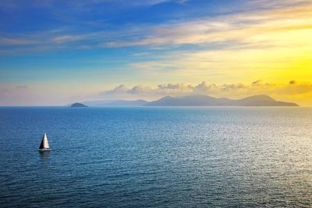 bateau voile: Île d'Elbe coucher de soleil vue depuis Piombino un yacht de bateau à voile. Mer Méditerranée. Toscane Italie Banque d'images