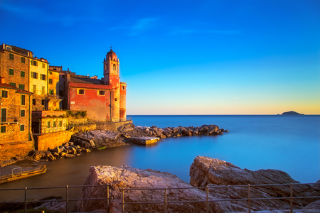 Tellaro rocks and old village on the sea. Church and houses on sunset. Long Exposure. Five lands Cinque Terre Liguria Italy Europe.