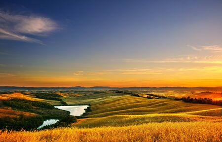 europe: Tuscany, Crete Senesi landscape near Siena, Italy, europe. Small lake, green and yellow fields, blue sky with clouds.