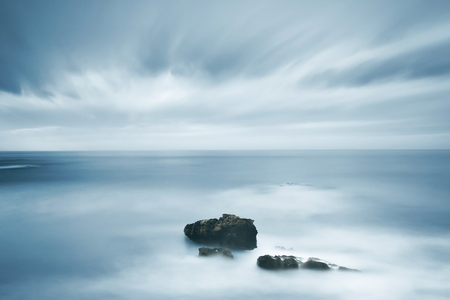 extreme weather: Dark rocks in a blue ocean under cloudy sky in a bad weather. Long exposure photography