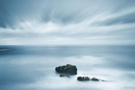 estado del tiempo: Rocas oscuras en un océano azul bajo el cielo nublado de mal tiempo. Fotografía de larga exposición