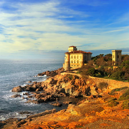 crepuscle: Boccale castle landmark on cliff rock and sea on warm sunset. Tuscany, Italy, Europe.
