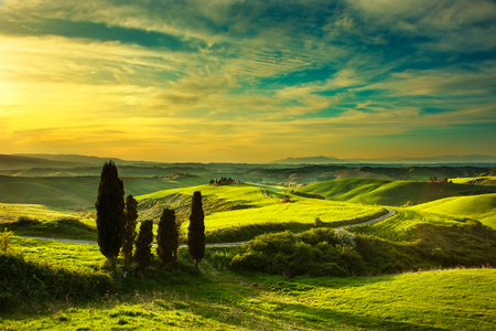 Tuscany, rural sunset landscape. Countryside farm, cypress trees, green field, sun light and cloud. Volterra, Italy, Europe.