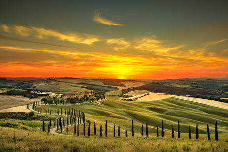 Tuscany, rural sunset landscape. Countryside farm, cypresses trees, green field, sun light and cloud. Italy, Europe. Stockfoto